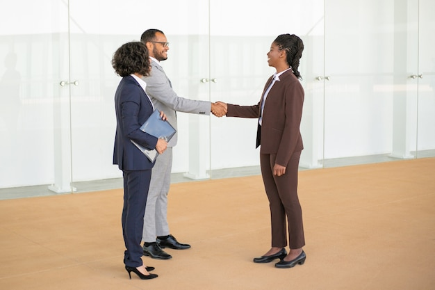 Gelukkige bedrijfscollega's die elkaar verwelkomen Gratis Foto