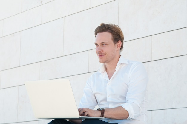 Gelukkige bedrijfsmens die aan laptop in openlucht werkt Gratis Foto