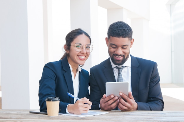 Gelukkige bedrijfsmensen die tablet gebruiken en bij bureau werken Gratis Foto