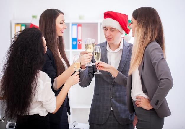 Gelukkige bedrijfsmensen in kerstmanhoeden bekijken camera en glimlachen terwijl het vieren van nieuwjaar Premium Foto