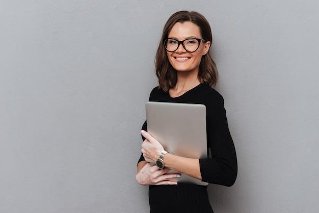 Gelukkige bedrijfsvrouw die in oogglazen tabletcomputer houden Gratis Foto