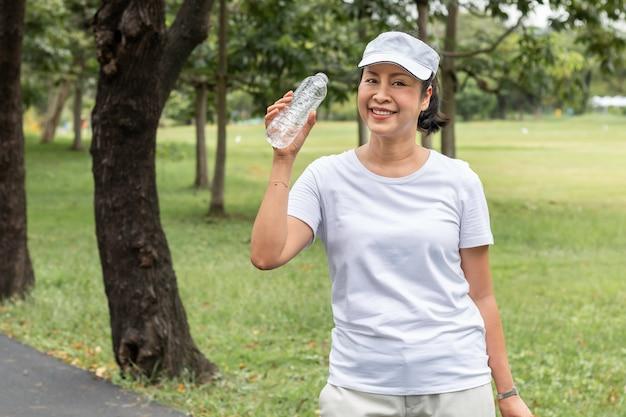 Gelukkige bejaarde aziatische glimlachende vrouw die zoet water in de zomer drinken bij het park. Premium Foto