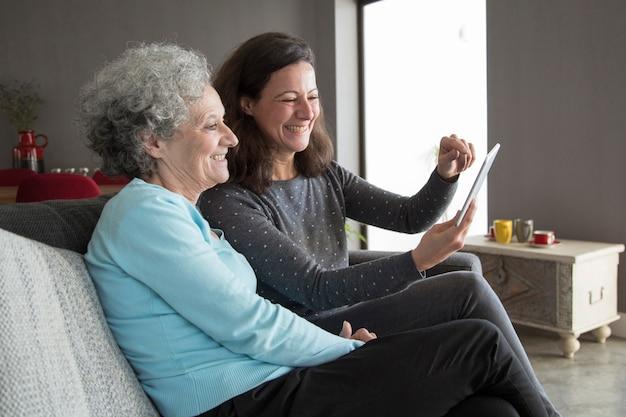 Gelukkige bejaarde en haar dochter die op tabletcomputer doorbladeren Gratis Foto