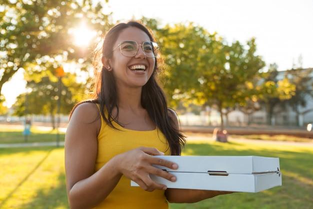 Gelukkige blije jonge vrouwen dragende pizza voor picknick Gratis Foto