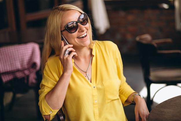 Gelukkige blonde haarvrouw die op telefoon spreekt Gratis Foto