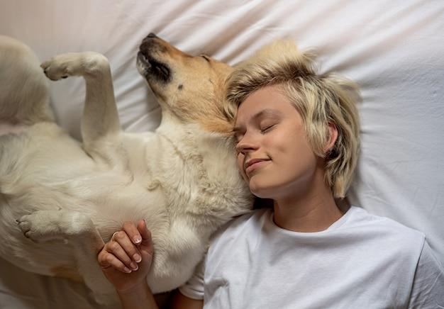Gelukkige blonde vrouw die in bed met haar herdershond legt Premium Foto