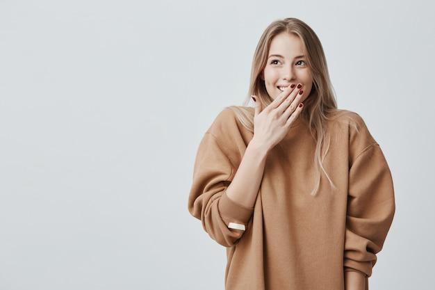 Gelukkige blondevrouw die haar mond met handen gaan die verrassing gaan zien die door en echtgenoot wordt voorbereid die glimlachen glimlachen Gratis Foto