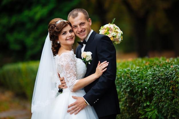 Gelukkige bruid en bruidegom op hun bruiloft knuffelen Premium Foto