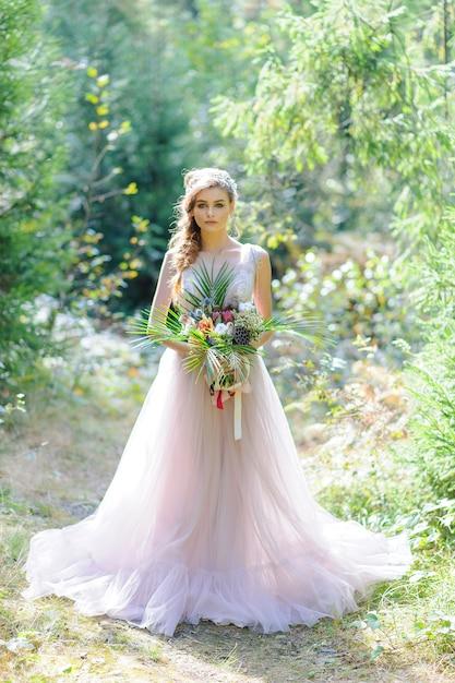 Gelukkige bruid in een roze trouwjurk. het meisje heeft een bruiloft boeket in haar handen. boho stijl huwelijksceremonie in het bos. Premium Foto