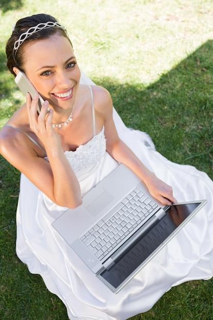 Gelukkige bruid met laptop die cellphone op gras gebruikt Premium Foto