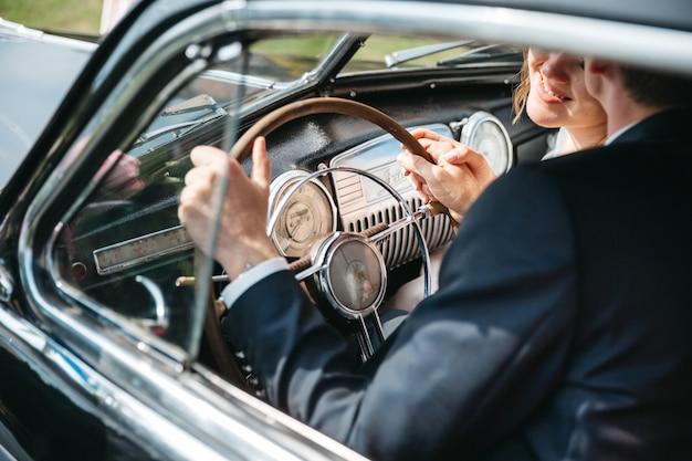 Gelukkige bruiden rijden in retro auto's Gratis Foto