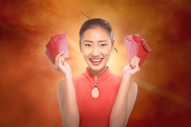 Gelukkige chinese vrouw die met cheongsam rode enveloppen houdt Premium Foto