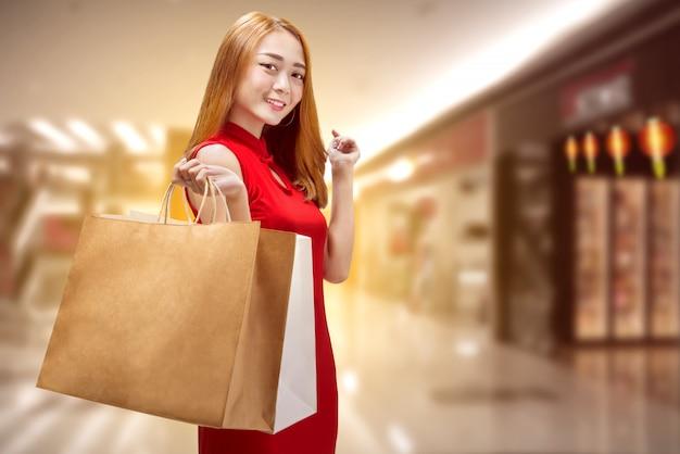 Gelukkige chinese vrouw die met traditionele kleren het winkelen zakken houdt Premium Foto