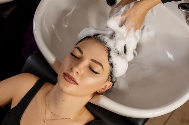 Gelukkige cliënt in een haarsalon die haar haar met shampoo wast. Premium Foto