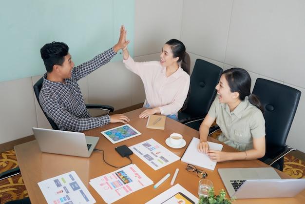 Gelukkige creatieve aziatische collega's die bij bureau in bureau zitten en hoog-vijf doen Gratis Foto