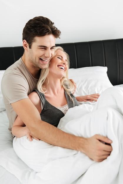 Gelukkige dame die terwijl het liggen in bed met haar man glimlacht Gratis Foto