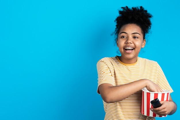 Gelukkige de popcornemmer en afstandsbediening van de vrouwenholding Gratis Foto
