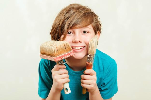 Gelukkige de verfborstels van de jongensholding. zoon helpt ouders om muur te schilderen. nieuw huis voor familie. home renovatie. Premium Foto