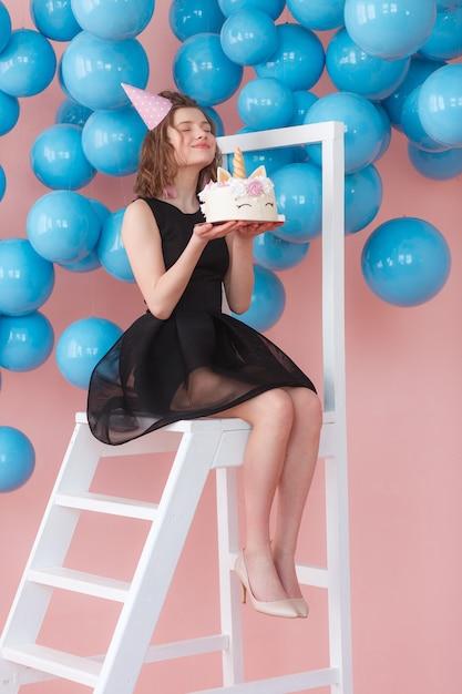 Gelukkige die de holdingseenhoorn van het tienermeisje gelaagde cake met schuimgebakjesclose-up wordt verfraaid. Gratis Foto
