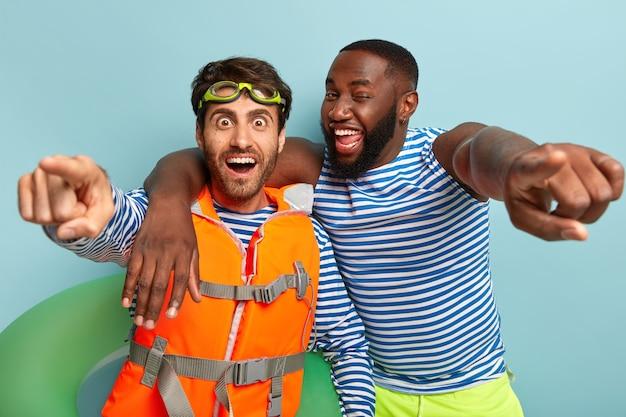 Gelukkige diverse jongens omhelzen elkaar en wijzen rechtstreeks naar de camera, hebben plezier op het strand, poseren met een reddingsboei Gratis Foto