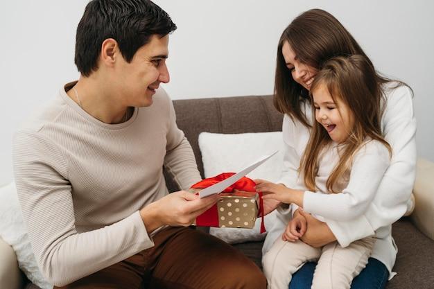 Gelukkige dochter die geschenk van ouders thuis ontvangt Gratis Foto