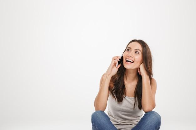 Gelukkige donkerbruine vrouwenzitting op de vloer en het spreken door smartphone terwijl het kijken weg over grijs Gratis Foto