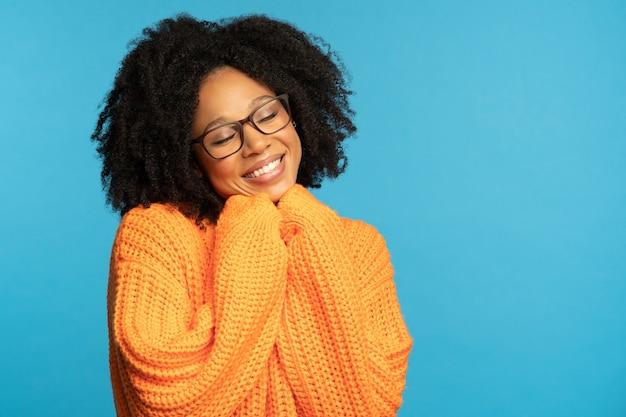 Gelukkige donkere duizendjarige vrouw met krullend haar draagt een oranje gebreide trui Premium Foto