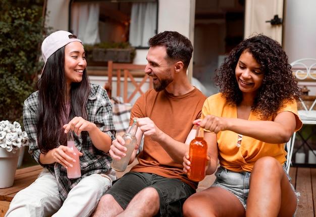 Gelukkige drie vrienden die hun vooraanzicht van de dranken openen Gratis Foto