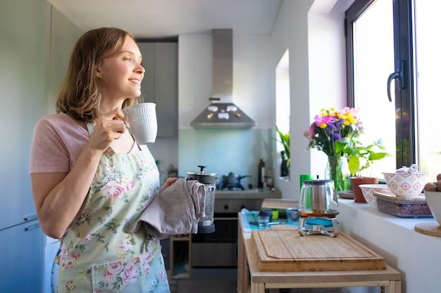 Gelukkige dromerige huisvrouw die een schort draagt, thee drinkt en uit het raam in haar keuken kijkt. thuis koken en theepauze concept Gratis Foto