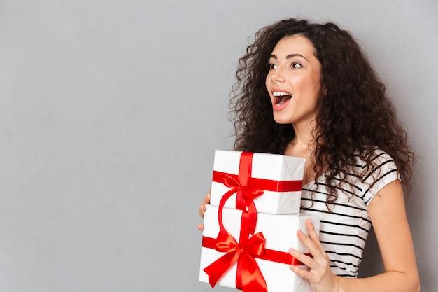 Gelukkige emoties van mooie vrouw in gestreepte t-shirt die twee gift verpakte dozen met rode bogen houden terwijl status over grijze muur Gratis Foto