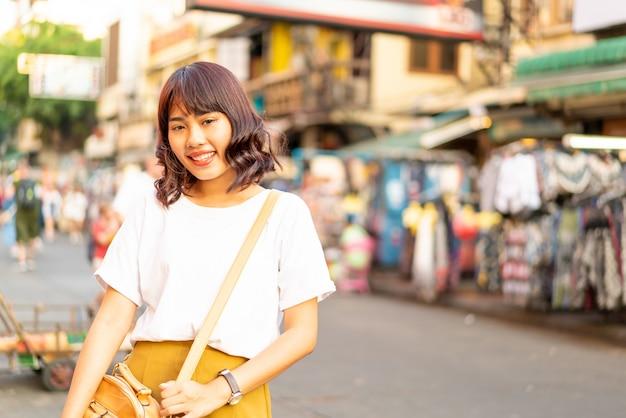 Gelukkige en mooie aziatische vrouw die bij khao sarn road, thailand reizen Premium Foto