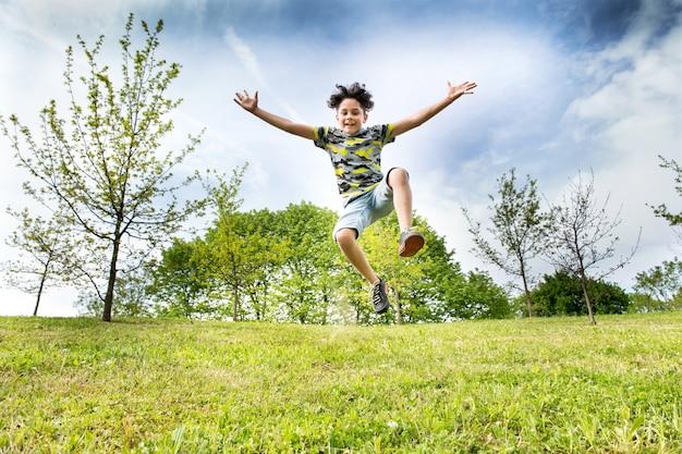 Gelukkige energieke jonge jongen die hoog in de lucht springt Premium Foto