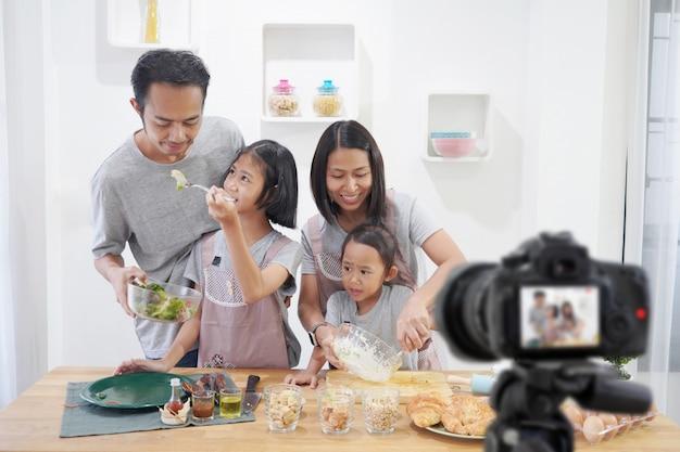 Gelukkige familie aziaat die een vlog-videoblogger digitale camera met het koken in de keukenruimte maken Premium Foto