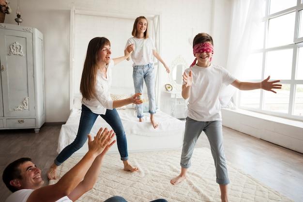 Gelukkige familie die bleekgele blinde thuis spelen Gratis Foto