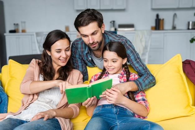 Gelukkige familie die een boek leest Gratis Foto