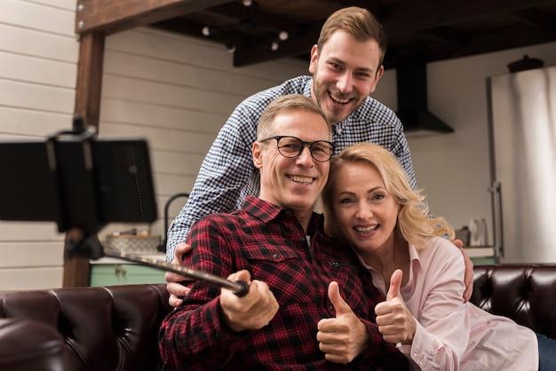 Gelukkige familie die en een selfie in de keuken glimlacht neemt Gratis Foto