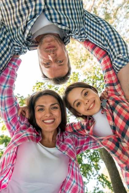 Gelukkige familie die krul in park vormen tegen hemel Gratis Foto