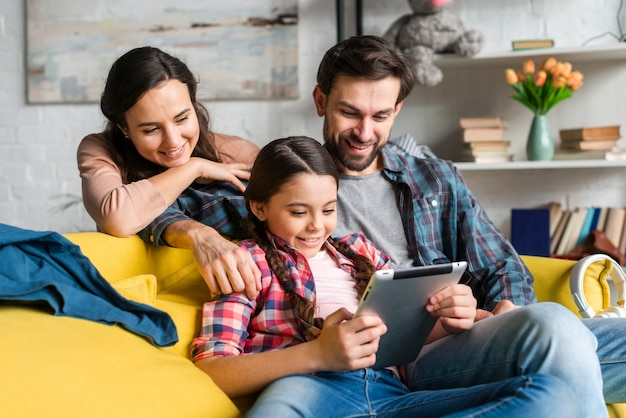 Gelukkige familie die op een tablet kijkt Gratis Foto
