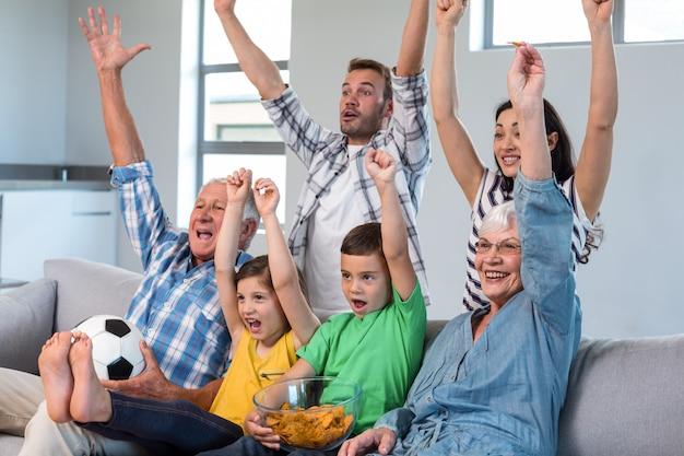 Gelukkige familie die op een voetbalwedstrijd thuis let Premium Foto