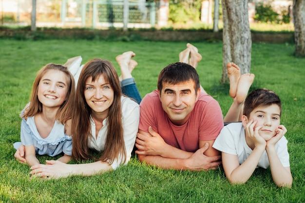 Gelukkige familie die op groen gras ligt en camera bekijkt Gratis Foto