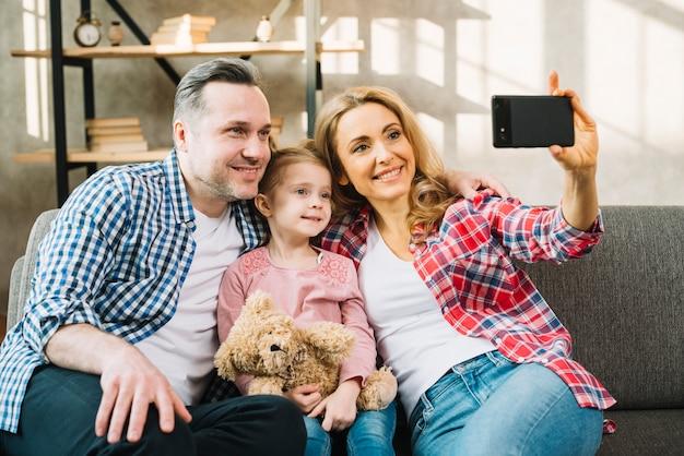 Gelukkige familie die selfie op bank nemen Gratis Foto