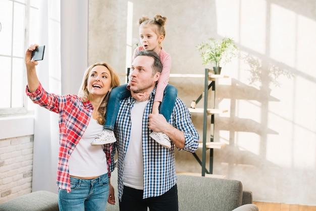 Gelukkige familie die selfie op cellphone thuis nemen Gratis Foto