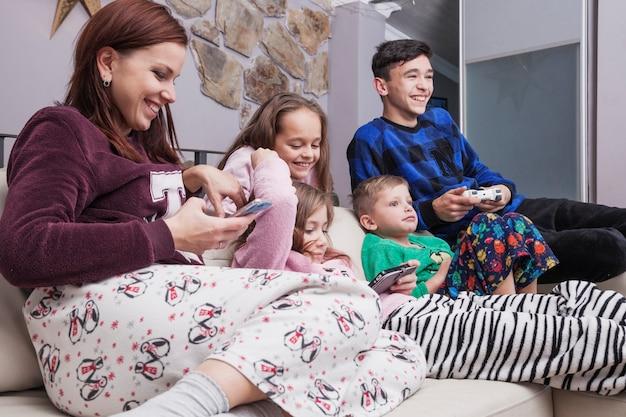 Gelukkige familie die technologieën op bank gebruiken Gratis Foto