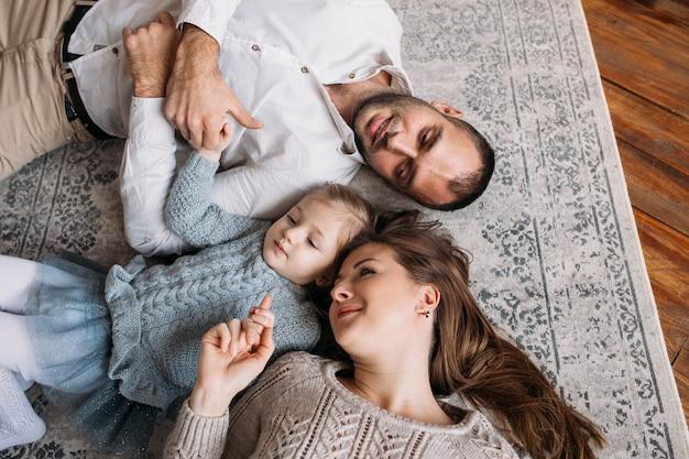 Gelukkige familie die thuis op de vloer ligt. bovenaanzicht Premium Foto