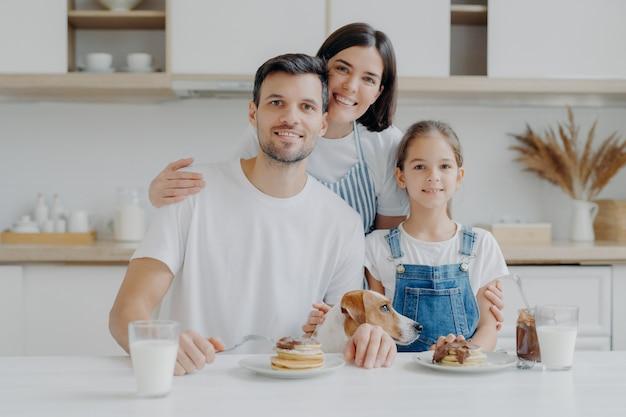 Gelukkige familie en hond poseren in gezellige keuken, eten verse zelfgemaakte pannenkoeken met chocolade en melk, kijken positief naar de camera. moeder in schort omhelst man en dochter, kookt graag voor hen Premium Foto
