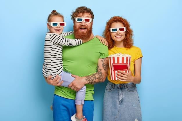 Gelukkige familie geniet van film of tekenfilm in de bioscoop, draag een 3d-bril, geamuseerd door coole geluids- en visuele effecten, eet een heerlijke snack. klein meisje op vaders handen, omhelst hem. mensen, vrije tijd, weekend Gratis Foto