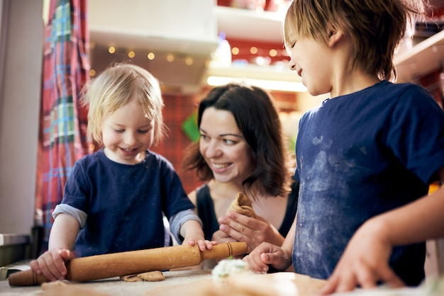 Gelukkige familie grappige jongens en hun moeder bereiden het deeg Premium Foto