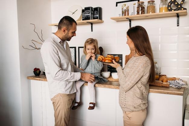 Gelukkige familie in de keuken die croissants eet Premium Foto