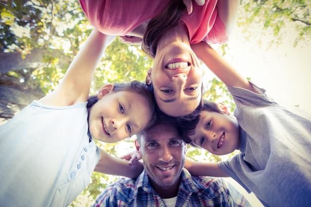 Gelukkige familie in het park die in cirkel samenweken Premium Foto