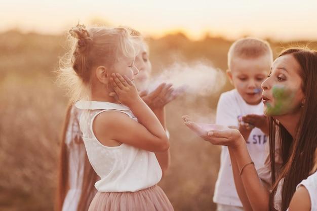 Gelukkige familie is besmeurd met verf. kinderen spelen met holi-festivalkleuren. concept voor indiase festival holi. nationaal, familiefeest, selectieve aandacht Premium Foto